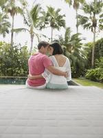 vista traseira de um jovem casal sentado no jardim