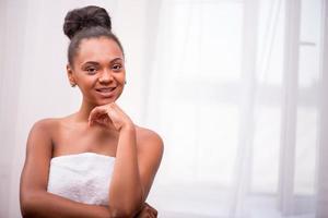 linda garota de pele escura na toalha branca foto