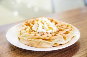 waffles sob a cobertura de caramelo com creme por cima foto