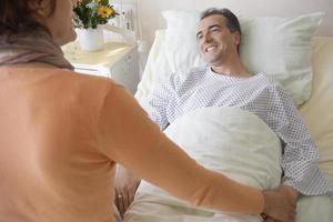 mulher visitando homem no hospital foto
