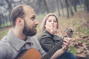 casal apaixonado tocando serenata com violão foto