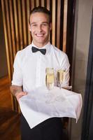 Garçom lindo e sorridente segurando uma bandeja de champanhe foto