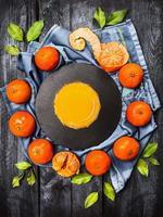 tangerinas frescas com folhas e copo de suco cítrico foto