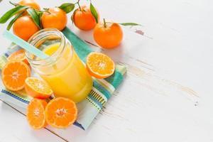 suco de tangerina em frasco de vidro com tangerinas cortadas foto
