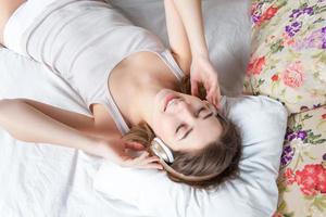 a jovem na cama ouvindo música, fones de ouvido foto
