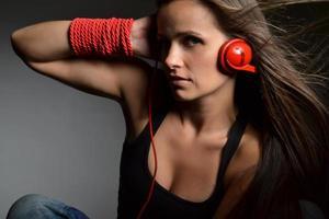 mulher jovem e bonita com os fones de ouvido vermelhos foto