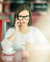 garota com um telefone no café foto