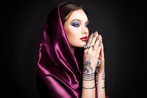 linda mulher em estilo oriental com mehendi em hijab foto