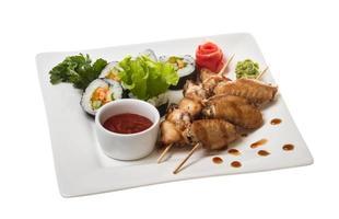 asas de frango búfalo no prato com sushi foto