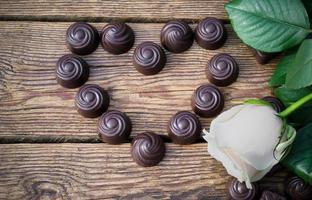 chocolates e flores em uma mesa de madeira foto