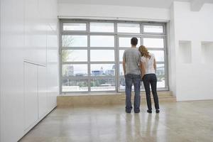 um casal em um apartamento vazio olhando pela janela grande foto