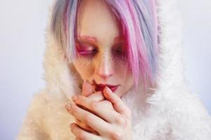 garota incomum com cabelo rosa, sinto frio em um casaco de pele foto