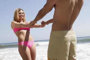 jovem casal na praia foto