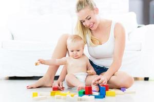 mãe e bebê brincando com blocos