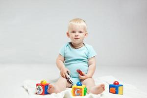 menino sorridente brincando com brinquedos educativos foto
