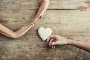 homem oferecendo um coração a uma mulher. foto