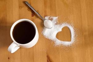 xícara de café preto, açúcar branco e formato de coração foto