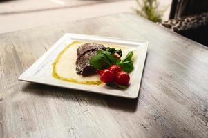 bife grelhado e cogumelos com tomate na mesa de madeira foto