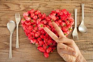 coração feito de rosas vermelhas em fundo de madeira