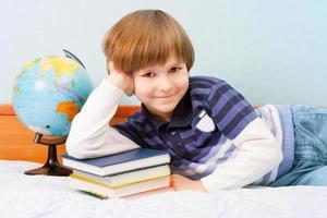 a criança com pilha de livro foto