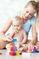 mãe e bebê brincando com blocos foto