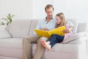 pai e filha casuais olhando para álbum de fotos