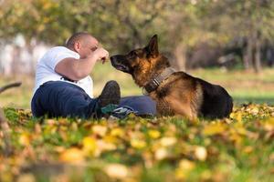 homem brincando com cão pastor alemão no parque foto