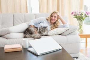 loira feliz com gato de estimação no sofá