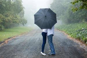 casal se beijando atrás do guarda-chuva foto