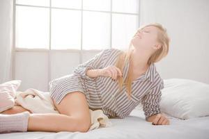 linda mulher sorridente posando em cama branca foto