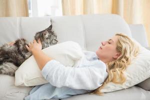 loira feliz com gato de estimação no sofá foto