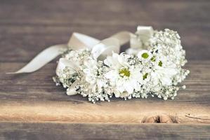 coroa de flores de camomila no chão de madeira foto