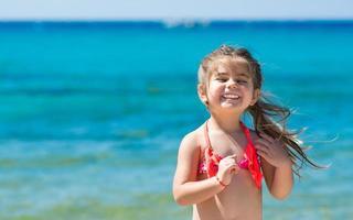 menina feliz e sorridente brincando na praia foto