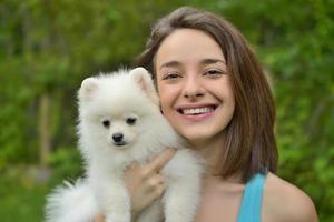 garota segurando cachorro spitz alemão do lado de fora e sorrindo para a câmera. foto