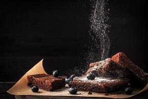 polvilhando brownie de chocolate com açúcar de confeiteiro horizontal foto