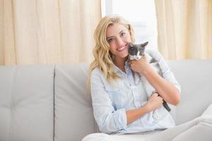 loira bonita com gatinho de estimação no sofá
