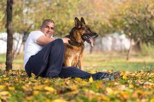 homem adulto sentado ao ar livre com seu pastor alemão foto