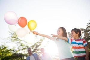 irmãos felizes segurando balões no parque foto
