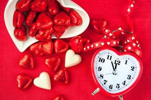 hora do doce amor. relógio vermelho em forma de coração com chocolates foto