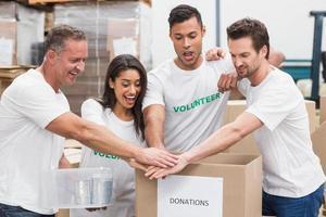 equipe de voluntários segurando uma caixa de doações