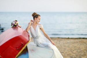 linda noiva sentada em um barco foto