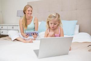 menina bonitinha com a mãe usando tablet e laptop