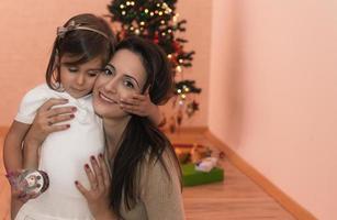 mãe e filha sentadas em frente a árvore de natal foto