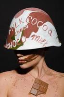 mulher com capacete de chocolate, camuflagem desviando o olhar foto