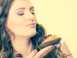 mulher de olhos fechados segura o bolo na mão