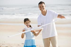 menina hispânica e pai brincando com um brinquedo na praia foto