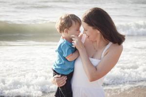 jovem mãe com filho brincando na praia foto