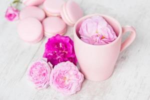 xícara de chá com rosa e macaroons