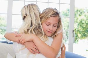 menina com os olhos fechados abraçando a mãe foto