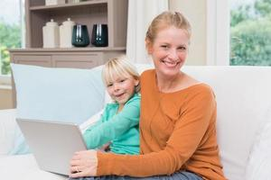 feliz mãe e filha no sofá usando laptop foto